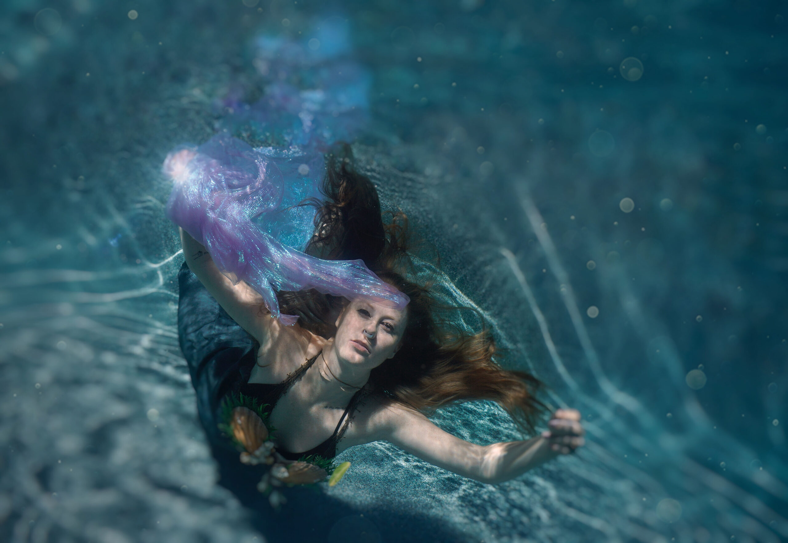 photo of a woman underwater wearing a mermaid costume and holding a purple scarf