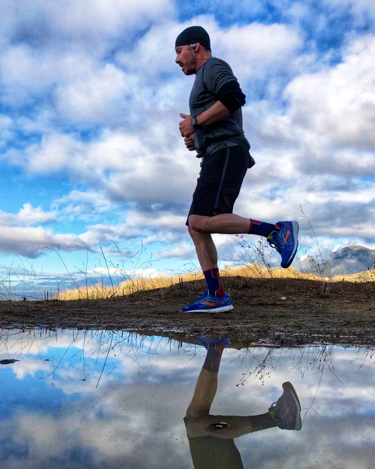 photo of man running, clouds in sky and water on the ground